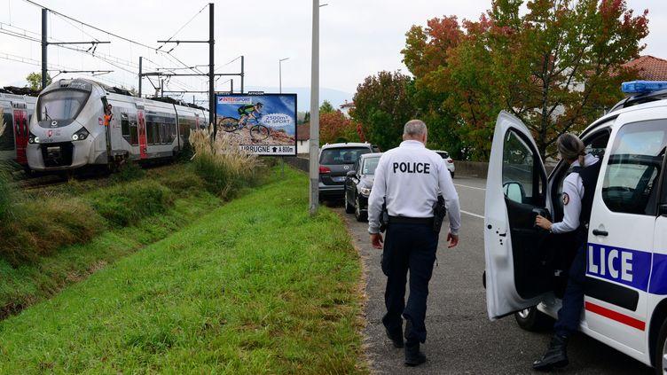 Un policier sort de son véhicule près d'un train à l'arrêtà hauteur de la gare de Saint-Jean-de-Luz-Ciboure après un accident qui a fait trois morts et un blessé grave, le 12 octobre 2021. (FRANCK LAHARRAGUE / AFP)