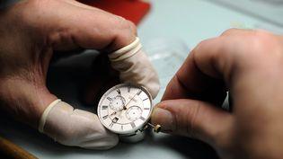 Un employé du fabricant de montres de luxe Leroy travaille à la fabrication de montres, le 20 décembre 2010 dans l'usine de Besançon. (JEFF PACHOUD / AFP)
