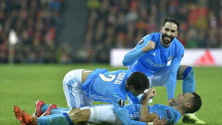 Lucas Ocampos (Marseille), au sol, célèbre son but contre Bilbao avec Hiroki Sakai et Adil Rami (ANDER GILLENEA / AFP)