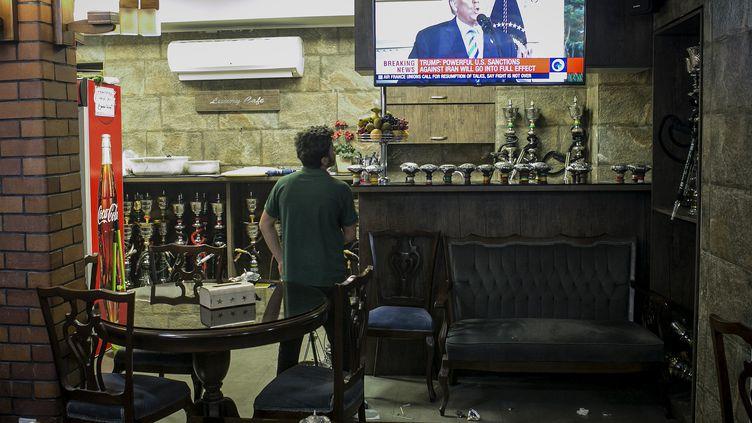 Un homme regarde à la télévision Donald Trump annoncer la sortie des Etats-Unis des accords sur le nucléaire iranien, dans le centre de Téhéran, le 8 mai 2018. (AHMAD HALABSIAZ / XINHUA)