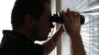 Un homme surveille à travers des stores. (MAXPPP)