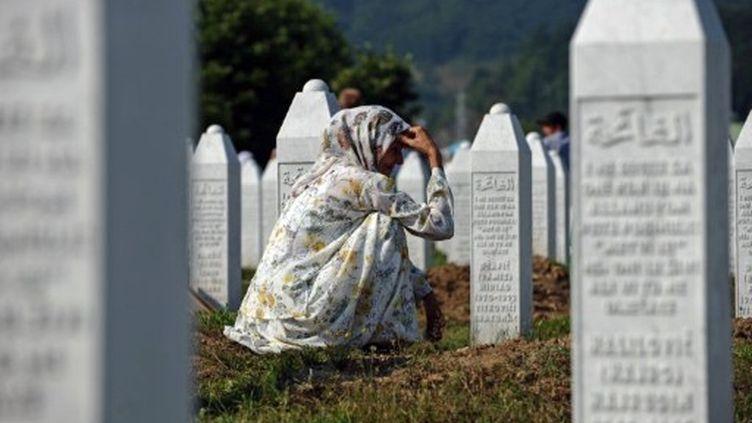 Une Bosniaque se recueille sur la tombe d'un proche dans le cimetière de Potocari, près de Srebrenica (11 juillet 2011). (ANDREJ ISAKOVIC / AFP)