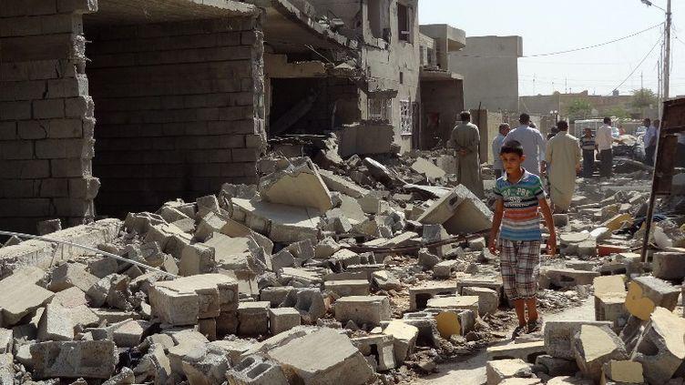 Un jeune irakien devant les ruines d'une maison après un attentat perpétré samedi 10 août 2013, àTouz Khourmatou, à 175 kilomètres au nord Bagdad. (MARWAN IBRAHIM / AFP)
