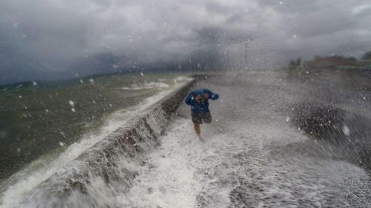 Un Philippin court pour échapper aux vagues provoquées par le typhon Melor, le 14 décembre 2015, à Legaspi, au sud de Manille (Philippines). (CHARISM SAYAT / AFP)