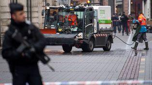 Après l'attentat à Strasbourg (Bas-Rhin), un officier de police se tient devant une scène de crime en cours de nettoyage, le 12décembre2018. (SEBASTIAN GOLLNOW / DPA / AFP)