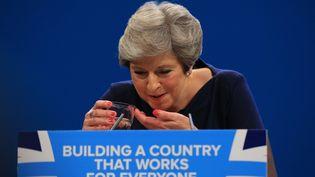 Theresa May, en pleine quinte de toux, boit de l'eau au cours de son discours devant les conservateurs britanniques, mercredi 4 octobre 2017 à Manchester. (LINDSEY PARNABY / ANADOLU AGENCY / AFP)