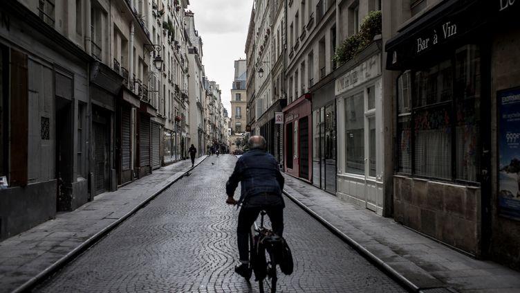 Un homme circule à vélo dans une rue de Paris. Photo d'illustration. (PHILIPPE LOPEZ / AFP)