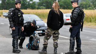 Des gendarmes parlent avec un participant à la rave-party à Redon, le 19 juin 2021. (FRANCK DUBRAY / MAXPPP)