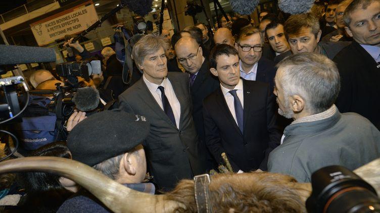 Manuel Valls et Stéphane Le Foll au Salon de l'agriculture, porte de Versailles, à Paris, le 29 février 2016. (MIGUEL MEDINA / AFP)