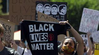 """Une manifestante soulève un tee-shirt portant le slogan """"Black lives matter"""" lors d'une manifestation à Washington, le 7 juin 2020. (JOSE LUIS MAGANA / AFP)"""
