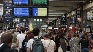 Des passagers scrutent les panneaux d'affichage, à la gare Montparnasse à Paris, le 17 juillet 2017. (GEOFFROY VAN DER HASSELT / AFP)