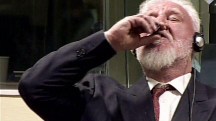 Capture d'écran d'une vidéo montrant SlobodanPraljak ingérant du cyanure de potassium, le 29 novembre 2017, au Tribunal pénal international pour l'ex-Yougoslavie, à La Haye (Pays-Bas). (INTERNATIONAL CRIMINAL TRIBUNAL / AFP)
