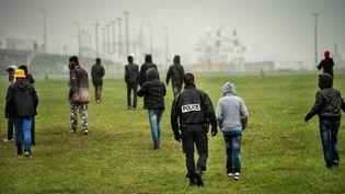 La police tente d'empêcher des migrants d'accéder aux camions à destination de la Grande-Bretagne, en octobre 2014 à Calais. (PHILIPPE HUGUEN / AFP)