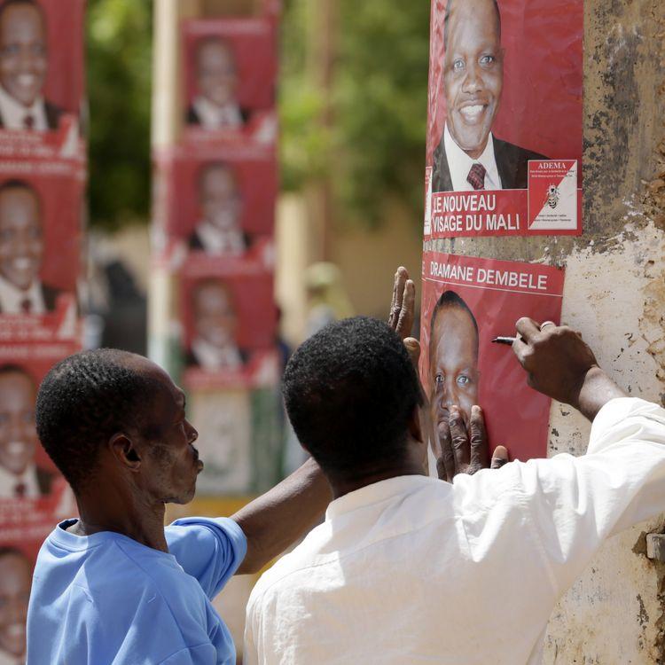 Des partisans du candidat Dramane Dembélé collent des affiches à Gao, dans le nord du Mali, le 25 juillet 2013. (KENZO TRIBOUILLARD / AFP)