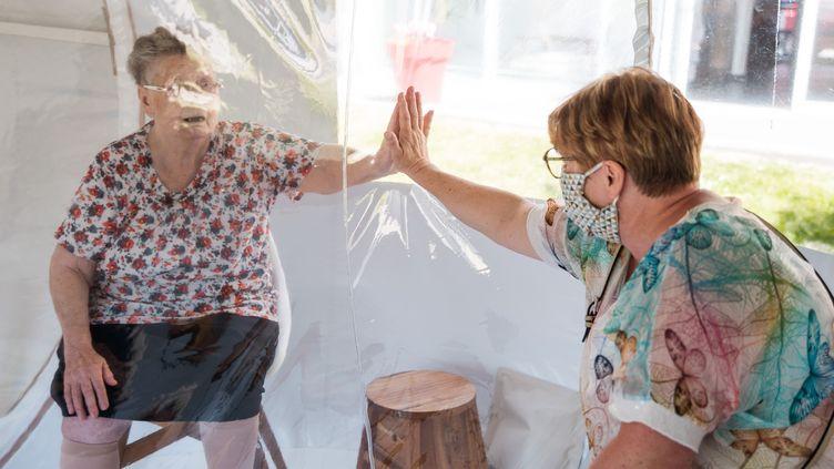 Une femme rend visite à une personne âgée dans une maison de retraite de Bourbourg (Nord), le 27 mai 2020. (JULIE SEBADELHA / HANS LUCAS / AFP)