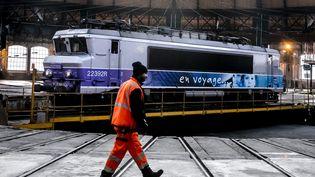 Un cheminot passe devant une locomotive lors de son retournement dans la Rotonde ferroviaire SNCF à Chambery, le 20 décembre 2016. Image d'illustration. (VINCENT ISORE / MAXPPP)