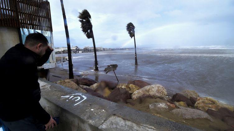 Un homme regarde par-delà la plage de La Malvarrosa, alors que la tempête Gloria frappe l'est de l'Espagne, le 20 janvier 2020. (JOSE JORDAN / AFP)
