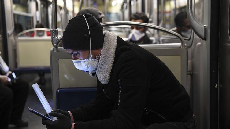 Un homme regarde son téléphone portable dans le métro parisien, le 23 mars 2020. (ALAIN JOCARD / AFP)