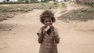 Lors d'un précédent épisode de disette, en décembre 2018, une fillette du village d'Ifotaka dans le sud de Madagascar, mange un complément alimentaire fourni par l'ONG Action contre la faim. (RIJASOLO / AFP)