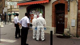 Des enquêteurs devant l'immeuble où a été retrouvé le corps d'une étudiante de 23 ans, à Toulouse (Haute-Garonne), le 4 août 2015. (  MAXPPP)