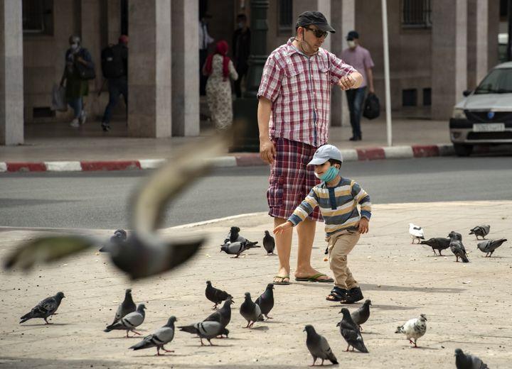 Un petit garçon avec un masque court après des pigeons, près de son père, à Rabat, le 16 juin 2020. (FADEL SENNA / AFP)