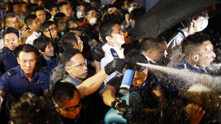 Un policier asperge des manifestants de gaz au poivre, le 16 octobre 2014 à Hong Kong (Chine). (CARLOS BARRIA / REUTERS)