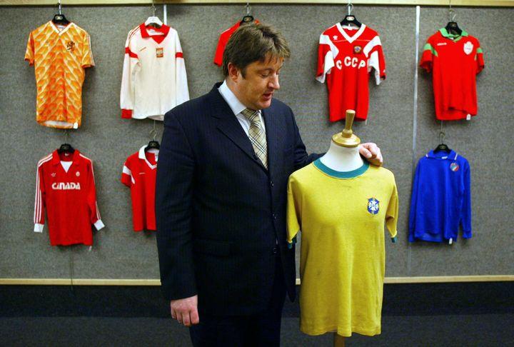 L'expert David Convery avec le maillot porté par Pelé lors de la finale du Mondial 1970, le 27 mars 2002 à Londres (Royaume-Uni). (ADRIAN DENNIS / AFP)
