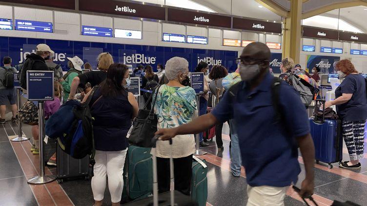 Des passagers à l'aéroport de Washington (Etats-Unis), le 1er août 2021. (DANIEL SLIM / AFP)
