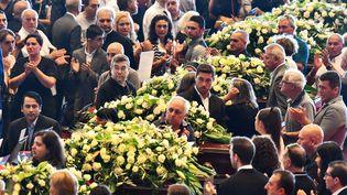 Les familles des victimes de l'effondrement du pont à Gênes se rassemblent près du cercueil de leur proche avant le début de la cérémonie d'hommage, le 18 août 2018. (ANDREA LEONI / AFP)