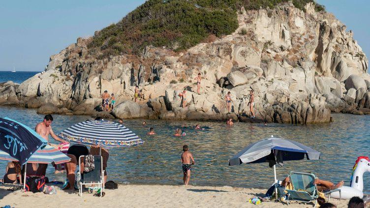 Des touristes prennent le soleil sur une plage de Kalamitsi, au nord de la Grèce, le 14 août 2020. (NICOLAS ECONOMOU / AFP)