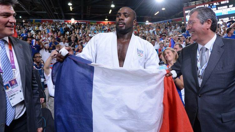 Le judoka Teddy Riner fête son titre olympique, le 28 juillet 2012 à Londres, en compagnie du maire de Levallois-Perret, Patrick Balkany. (EMMANUEL DUNAND / AFP)