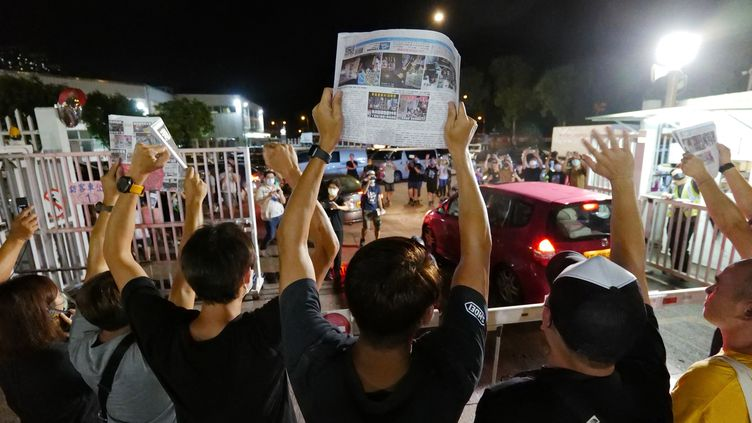 Des journalistes d'Apple Daily tiennent des exemplaires de la dernière édition du journal contraint de fermer ses portes, à Hong Kong, le 24 juin 2021. (DANIEL SUEN / AFP)