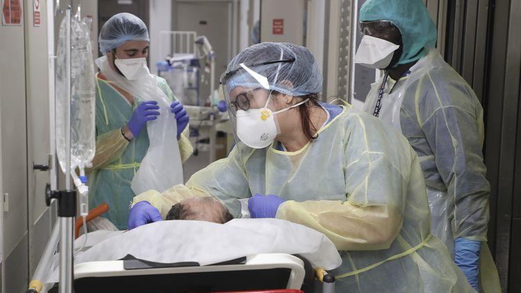 Des soignants autour d'un patient atteint du Covid-19, dans une clinique de Bagnolet, le 8 avril 2020. (LUDOVIC MARIN / AFP)