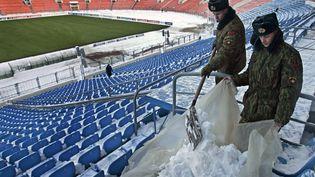 Des soldats enlèvent la neige des tribunes du stade du BATE Borisov, en Biélorussie, avant un match de Ligue des champions, le 25 novembre 2008. (SERGEI GRITS/AP/SIPA / AP)