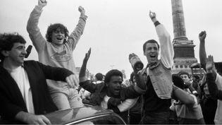 Des partisans de François Mitterrand célèbrent sa victoire à l'élection présidentielle, le 10 mai 1981, place de la Bastille, à Paris. (MORVAN / SIPA)