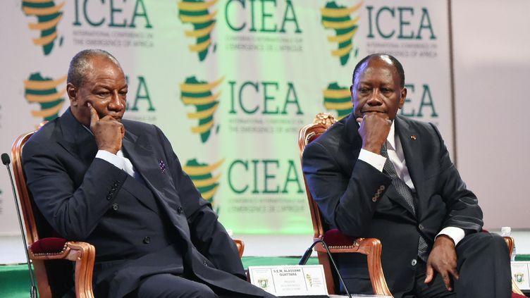 """Le président guinéen, Alpha Condé (à gauche) et son homologue ivoirien Alassane Ouattara, lors d'une conférence internationale le 28 mars 2017 à Abidjan. Les deux chefs d'Etat sont au cœur d'une polémique sur le """"syndrome du 3ème mandat"""" en Afrique. (SIA KAMBOU / AFP)"""