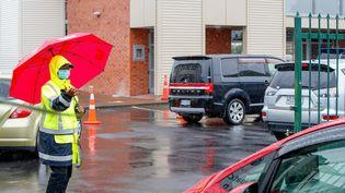 Un agent de sécurité contrôle les automobilistes en attente d'un test de dépistageau lycée de Papatoetoe (Nouvelle-Zélande), le 15 février 2021. (DAVID ROWLAND / AFP)