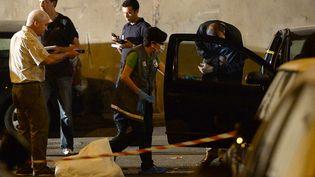 Des policiers dans une rue du 15e arrondissement de Marseille (Bouches-du-Rhône), où un homme a été tué de plusieurs balles, dans la nuit du 19 au 20 juin 2013. (BHORVAT / AFP)