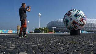 Devant l'Allianz Arena de Munich, le ballon officiel et quelques affiches montrent que le stade accueillera des matchs de l'Euro 2021. Mais ailleurs dans la ville, il n'y a quasiment pas de drapeaux ou d'affiches. (CHRISTOF STACHE / AFP)