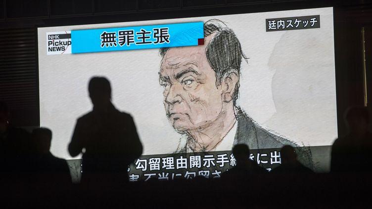 Des passants devant un dessin de Carlos Ghosn, le PDG de Renault, sur un écran de télévision, le 8 janvier 2019 à Tokyo (Japon). (BEHROUZ MEHRI / AFP)