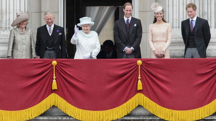 La reine d'Angleterre est apparue, au balcon du palais de Buckingham (Londres)décoré de lourds drapés rouge et or aux côtés de cinq membres de la famille royale, dont son fils, le prince Charles, et ses petit-fils William et Harry, mais en l'absence de son mari, le prince Philip hospitalisé depuis lundi 5 juin 2012 (LEON NEAL / AFP)