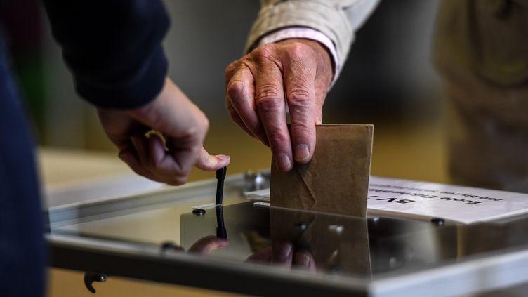 Un électeur glisse son bulletin de vote dans l'urne (photo d'illustration). (CHRISTOPHE ARCHAMBAULT / AFP)