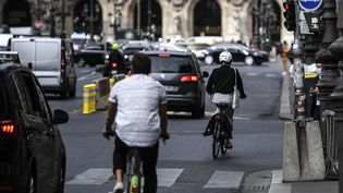 Une cycliste grille un feu rouge dans le trafic parisien, le 23 septembre 2020. (CHRISTOPHE ARCHAMBAULT / AFP)