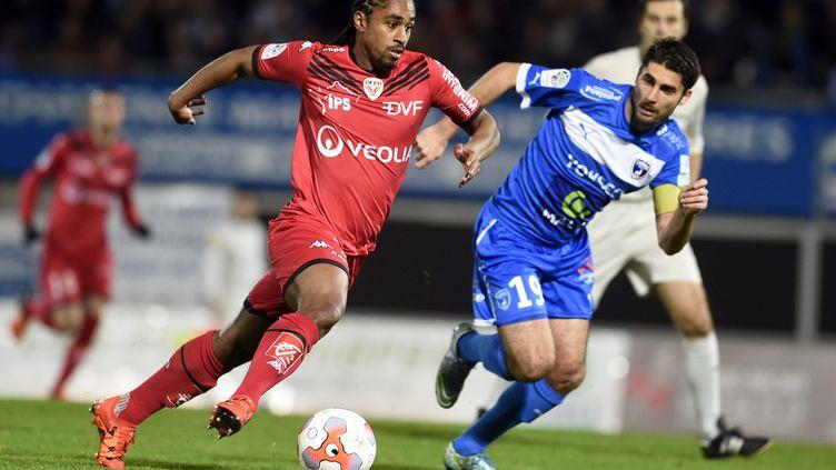 Le capitaine des Chamois Niortais, Jimmy Roye (bleu), au duel avec l'attaquant dijonnais, Wesley Saïd. (MARIE DELAGE / MAXPPP)