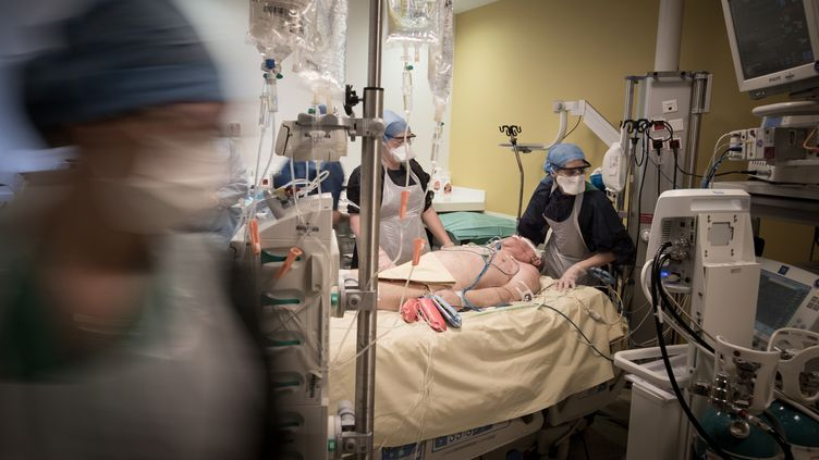 Des soignants s'occupent d'un patient atteint par le coronavirus dans l'unité de soins intensifs de l'Hôpital de Lariboisière à Paris le 27 avril 2020. (JOEL SAGET / AFP)