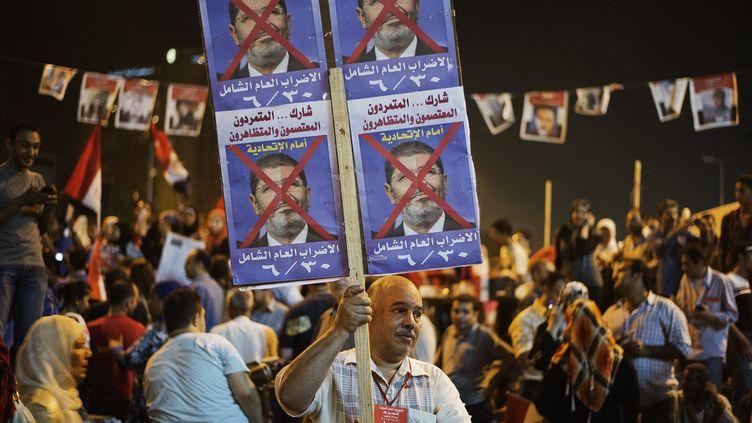 Un Egyptien brandit une pancarteanti-Morsi place Tahrir, au Caire, le 26 juin 2013. (GIANLUIGI GUERCIA / AFP)