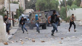 Des Palestiniens fuient les forces israéliennes le 6 octobre 2015. (NEDAL ESHTAYAH/MAXPPP)
