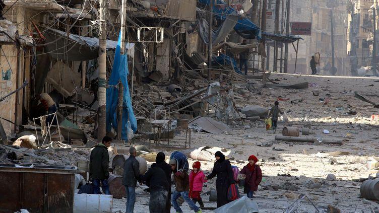 Des civils marchent dans les décombres d'un quartier de l'est d'Alep (Syrie), le 28 novembre 2016. (ABDALRHMAN ISMAIL / REUTERS)