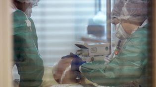 Des médecins prennent en charge un malade infecté par le coronavirus, le 31 mars 2020, au CHRU de Tours (Indre-et-Loire). (GUILLAUME SOUVANT / AFP)