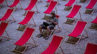 """Un homme attend le début d'un spectacle dans la """"Cour d'Honneur du Palais des Papes"""" à Avignon, le 18 juillet 2020. (CLEMENT MAHOUDEAU / AFP)"""